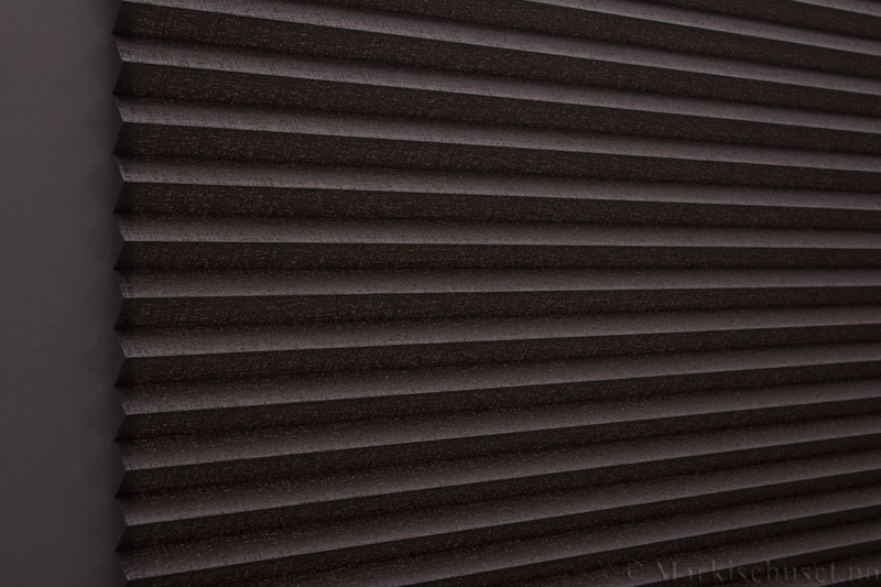 Plisségardin tekstil Manhattan Gloss 290581-4812 Bronse Antrasitt farge. Bildet er tatt med lys bakfra.