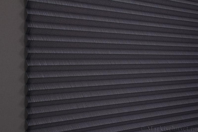 Plisségardin tekstil Lino Gloss 290588-1251 Sølv/Antrasitt farge. Bildet er tatt med lys bakfra.