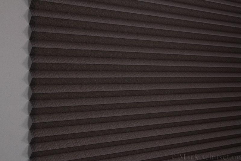 Plisségardin tekstil Lino Gloss 290588-4812 Bronse/Antrasitt farge. Bildet er tatt med lys bakfra.