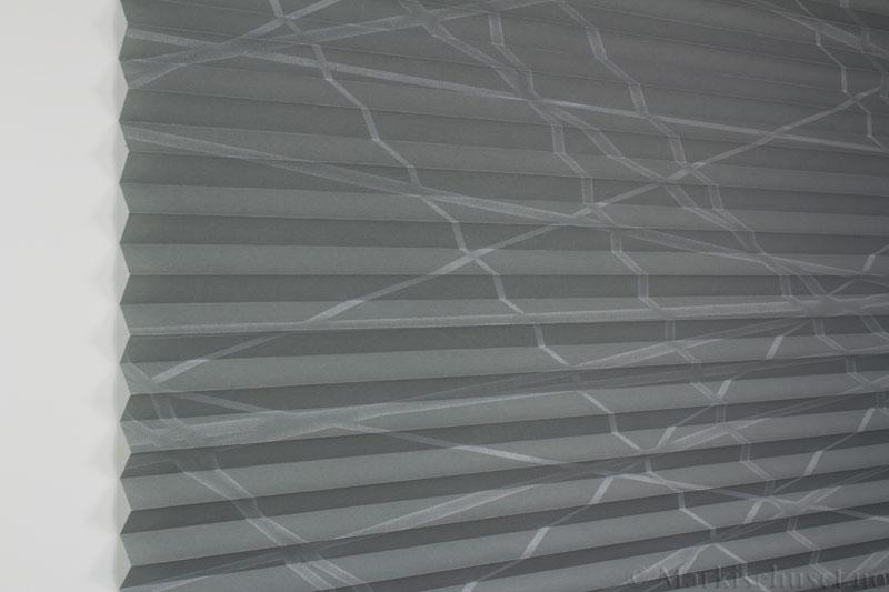 Plisségardin tekstil Laser Gloss 290594-1500 Sølv/Grå farge. Bildet er tatt med lys forfra.