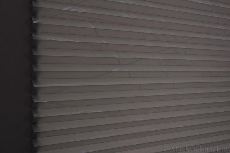Plisségardin tekstil Laser Gloss 290594-1500 Sølv/Grå farge. Bildet er tatt med lys bakfra.