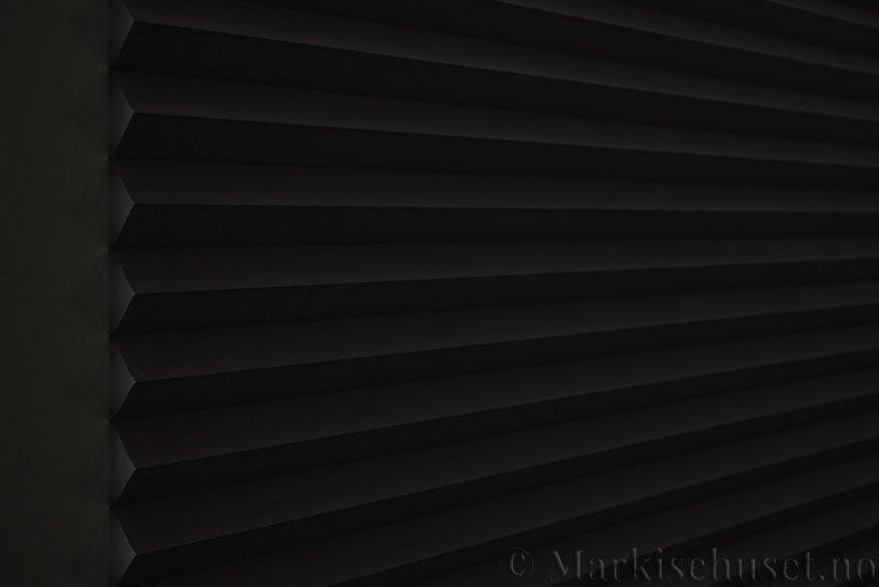 Plisségardin tekstil Niluna 290705-1510 Mellomgrå farge. Bildet er tatt med lys bakfra og litt lys forfra.