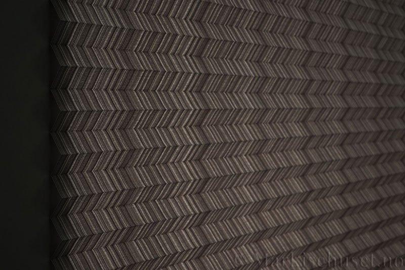 Plisségardin tekstil Mistral 290707-1250 Grå/Sort farge. Bildet er tatt med lys bakfra.