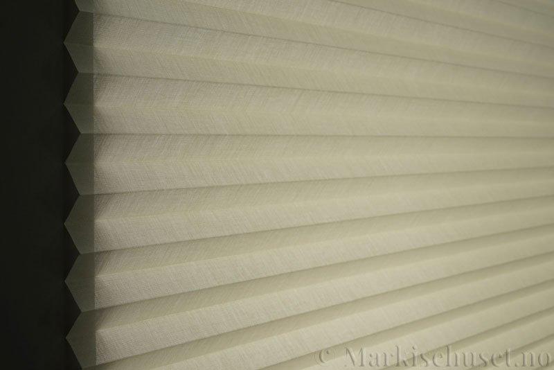 Plisségardin tekstil Lumina Sheer Dustblock 290708-0500 Bomullshvit farge. Bildet er tatt med lys bakfra.