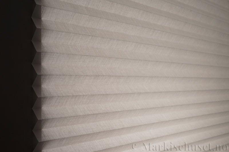 Plisségardin tekstil Lumina Sheer Dustblock 290708-0999 Delfingrå farge. Bildet er tatt med lys bakfra.