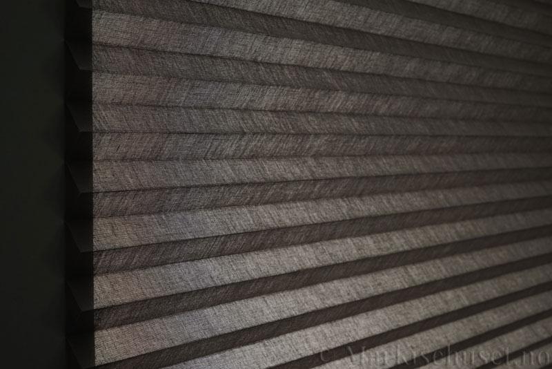 Plisségardin tekstil Lumina Sheer Dustblock 290708-1510 Mellomgrå farge. Bildet er tatt med lys bakfra.