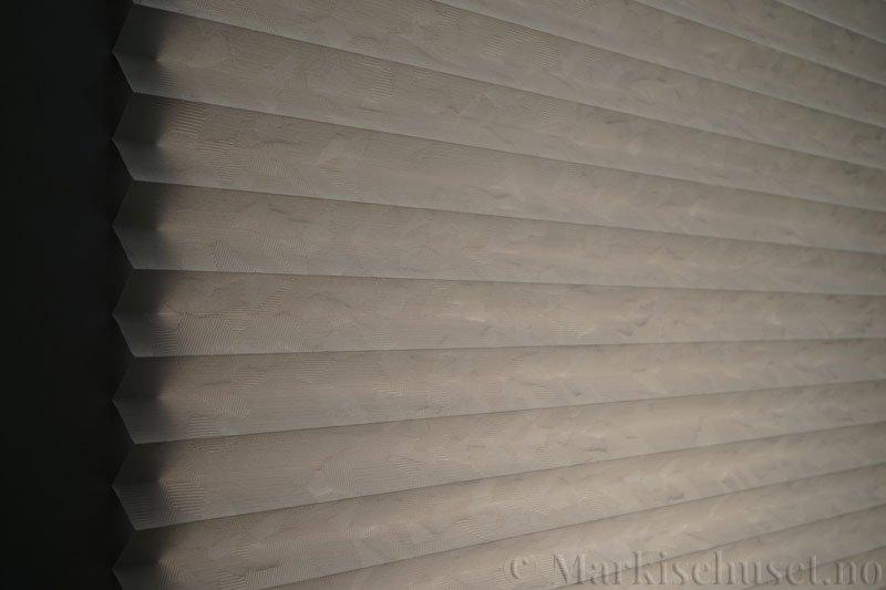 Plisségardin tekstil Crystal Topar Plus 290717-1320 Elefantgrå farge. Bildet er tatt med lys bakfra.