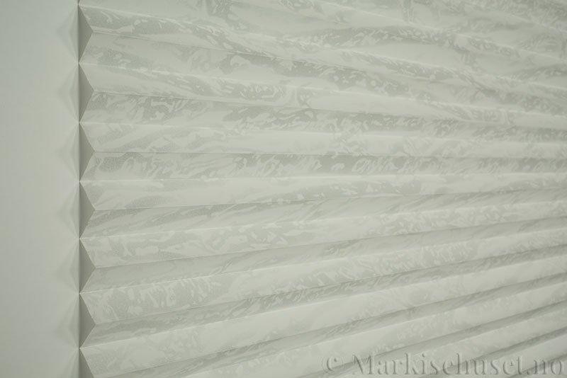 Plisségardin tekstil Abora Gloss 290724-1250 Sølv/Hvit farge. Bildet er tatt med lys forfra.