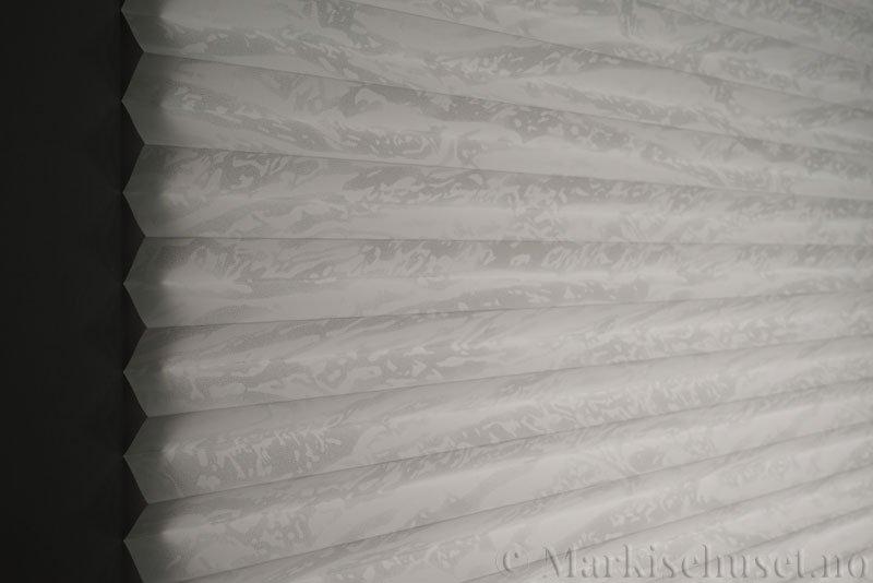 Plisségardin tekstil Abora Gloss 290724-1250 Sølv/Hvit farge. Bildet er tatt med lys bakfra.